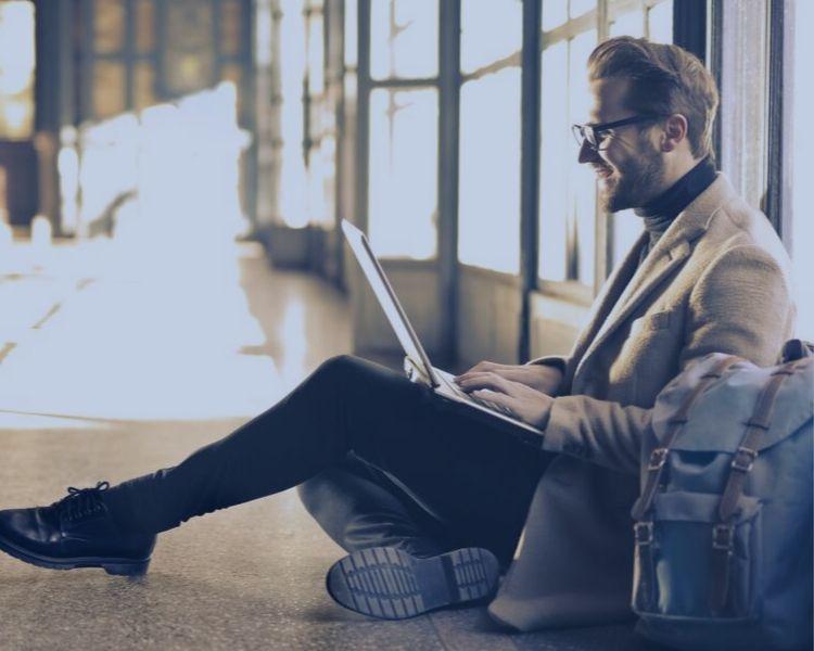 Man sat on the floor on a laptop