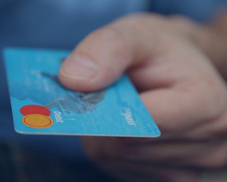 Hand holding a blue debit card