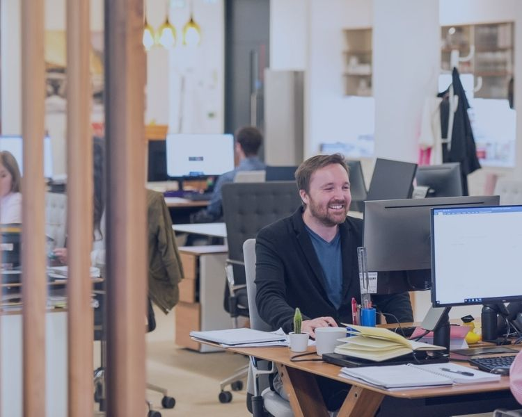 Office scene with a focus on a man at his desk in a black jacket, smiling