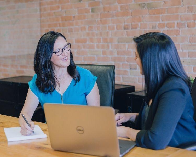 two women talking in front of laptop
